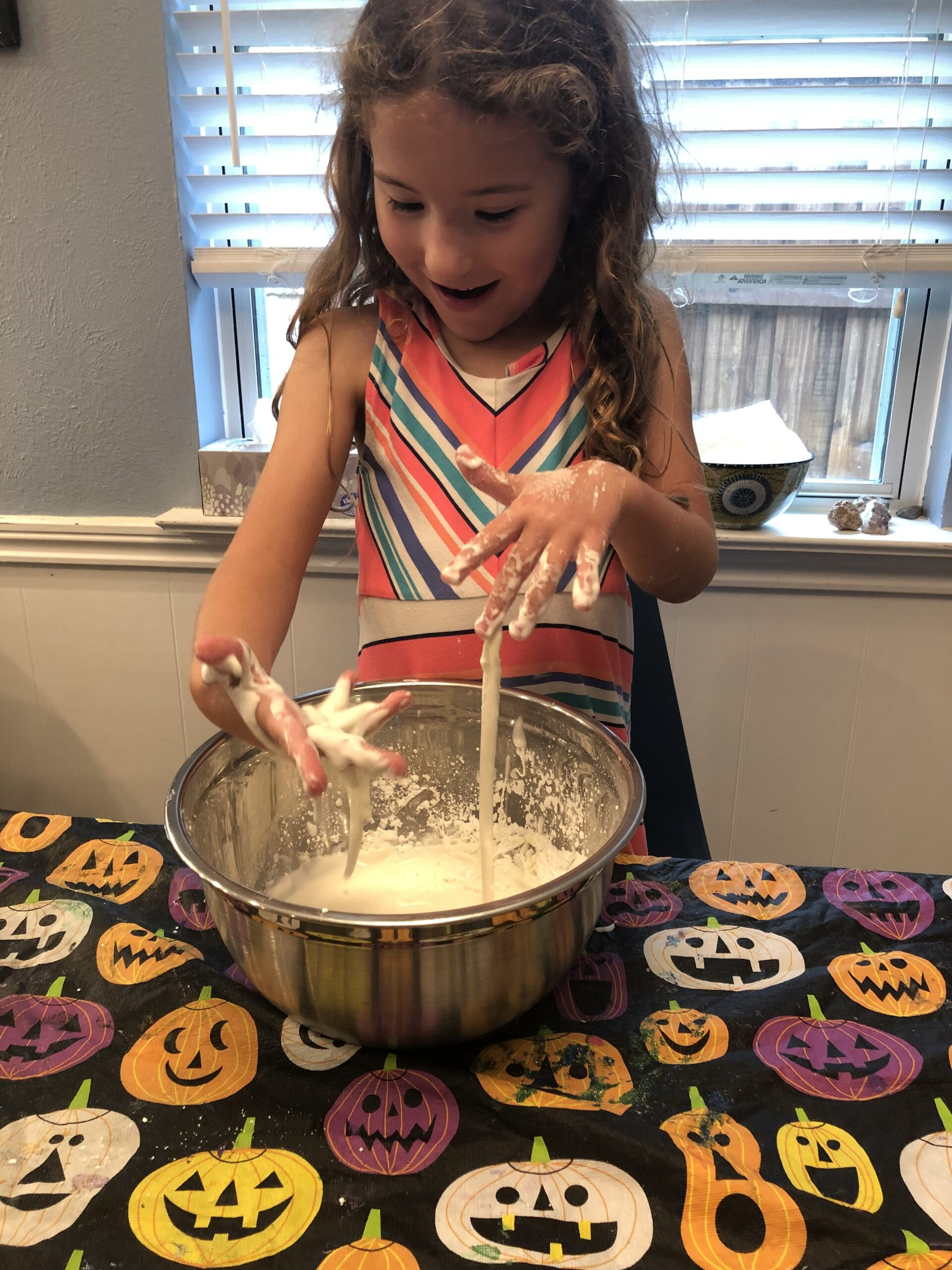 Child doing a science experiment- playing with oobleck